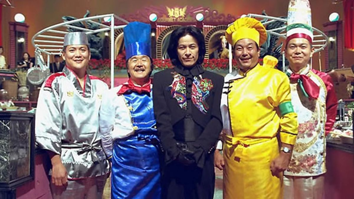 Four Iron Chef Japan cast members in bright outfits with The Chairman in the middle.
