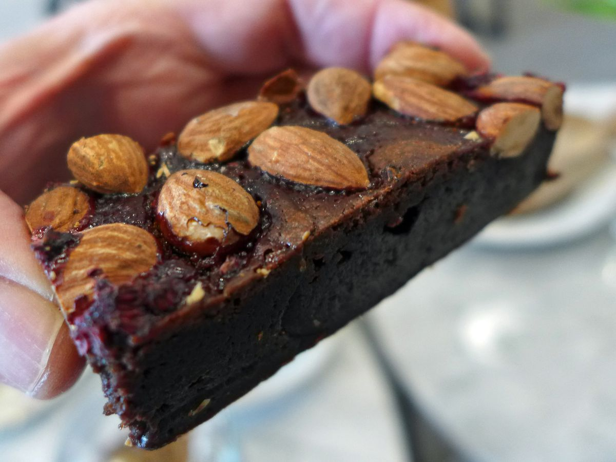 A dark chocolate brownie topped with whole almonds held between two fingers