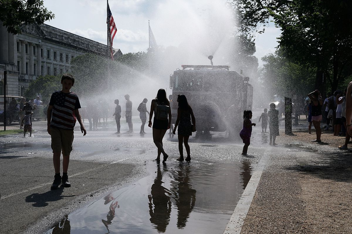 People cool themselves in water spray from a fire truck outside the annual Smithsonian Folklife Festival on Independence Day July 4, 2018 in Washington, DC.