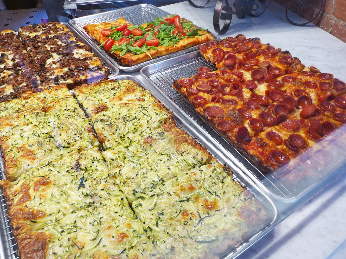 Four square pies cut into slices with various toppings, including mozzarella and zucchini.