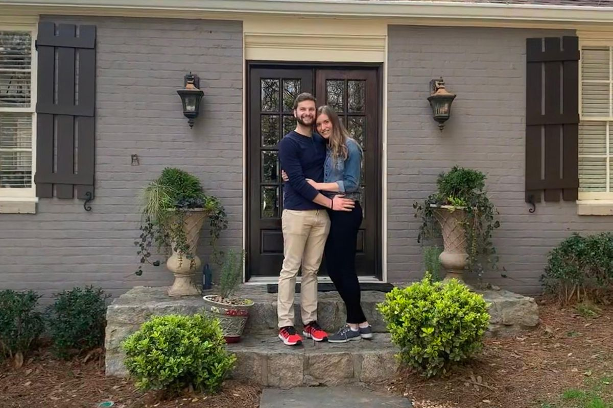 A couple stands in front of their new home in Atlanta's Tuxedo Park neighborhood.