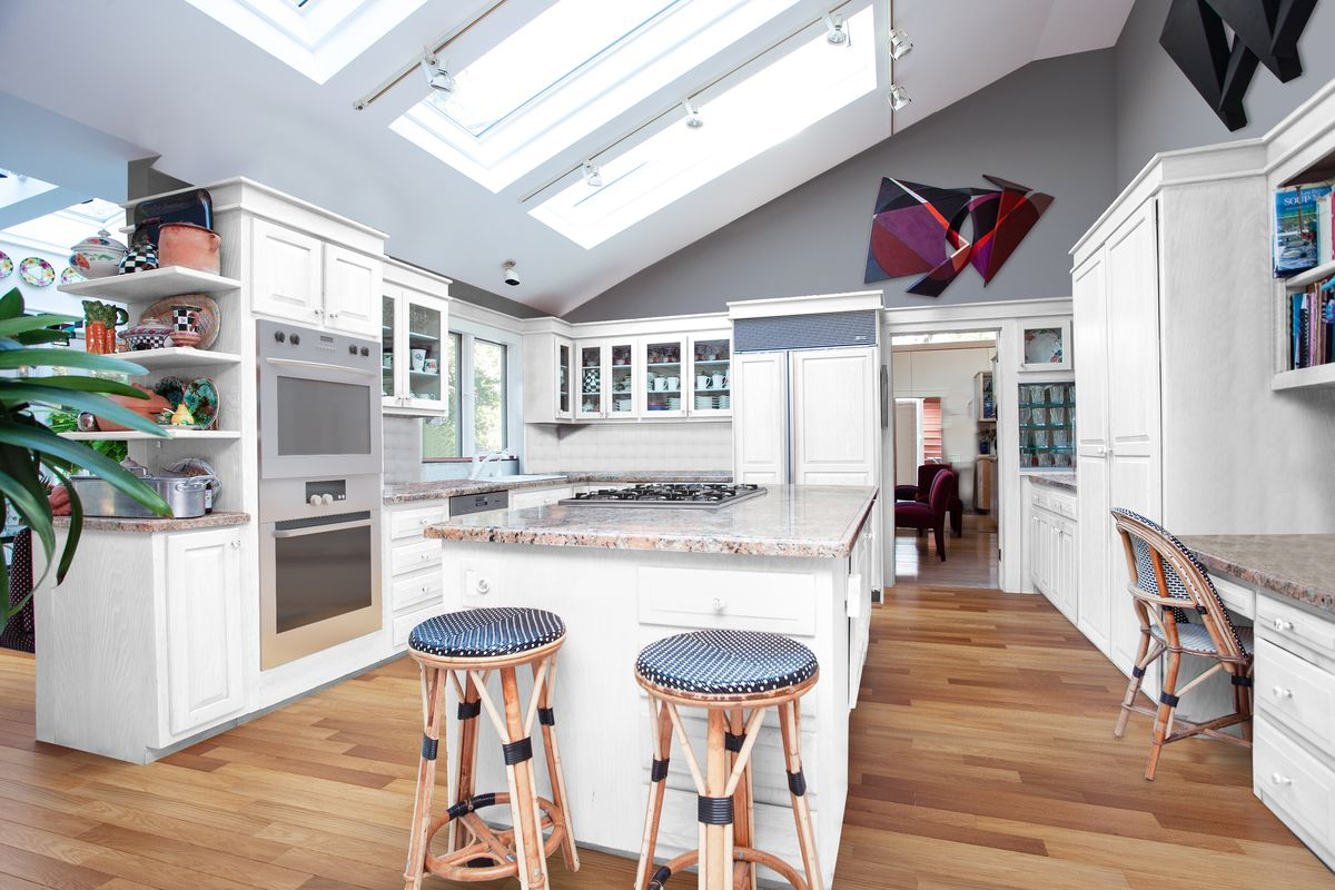 A white and gray kitchen features a large island, two French-style bar stools, and skylights.