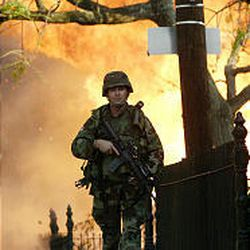 A soldier patrols the street near a large house fire in the Garden District in New Orleans on Tuesday.