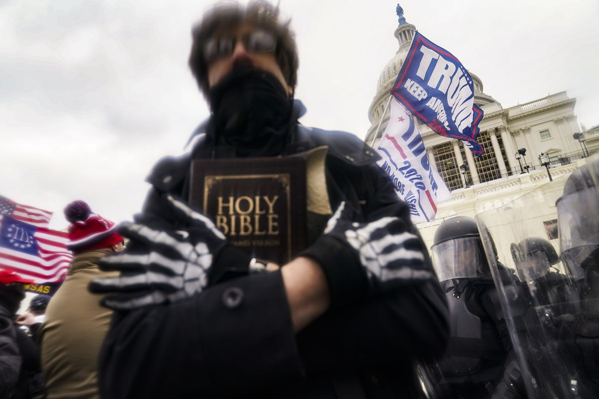 In this Wednesday, Jan. 6, 2021 file photo, a man holds a Bible as Trump supporters gather outside the Capitol in Washington. The Christian imagery and rhetoric on view during this month's Capitol insurrection are sparking renewed debate about the societal effects of melding Christian faith with an exclusionary breed of nationalism.