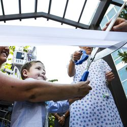 Dash Johnson, 4, left, a patient at Primary Children's Hospital, cuts the ribbon during the reopening of the Angel Garden at the hospital in Salt Lake City on Monday, Aug. 1, 2016. The redesigned garden includes more than 1,000 new plants and trees, as well as legacy monuments, including the Butterfly Angel statue, a commissioned 5-foot bronze. Dash's family spearheaded renewal project.