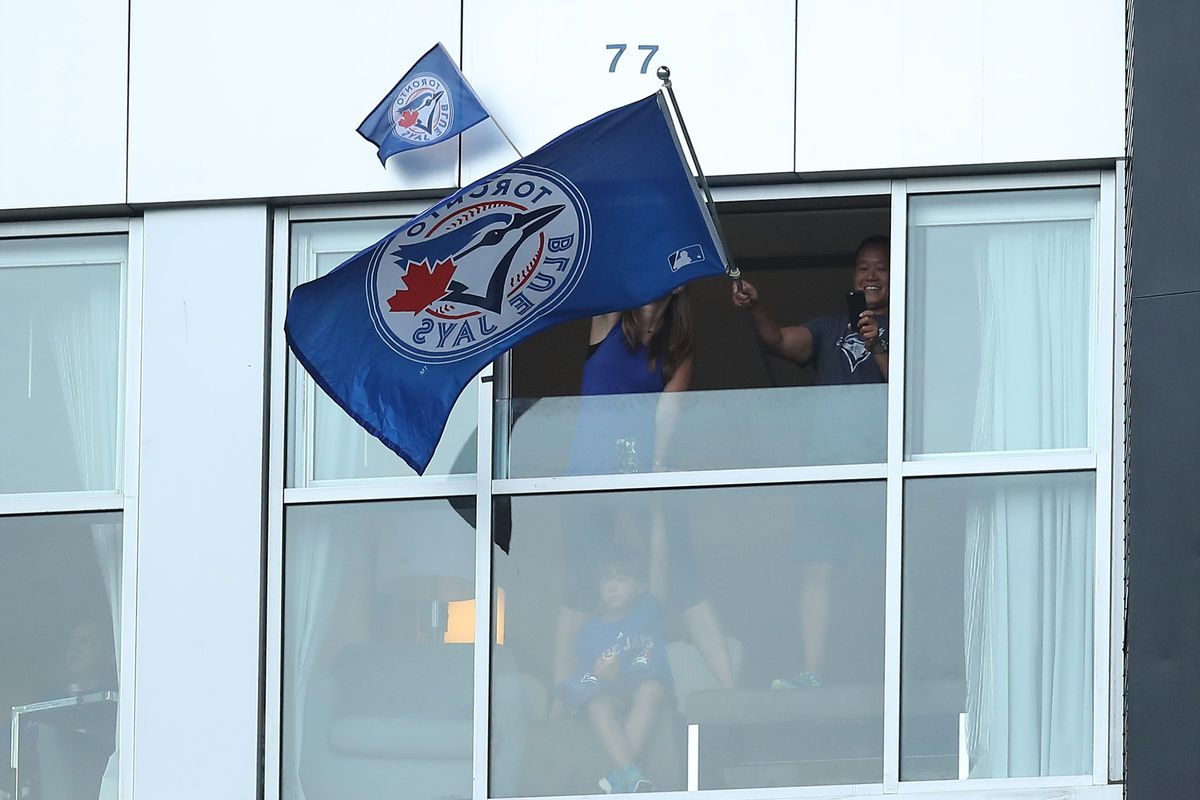 Blue Jays fans wave a flag from their hotel window at the Rogers Centre, Toronto
