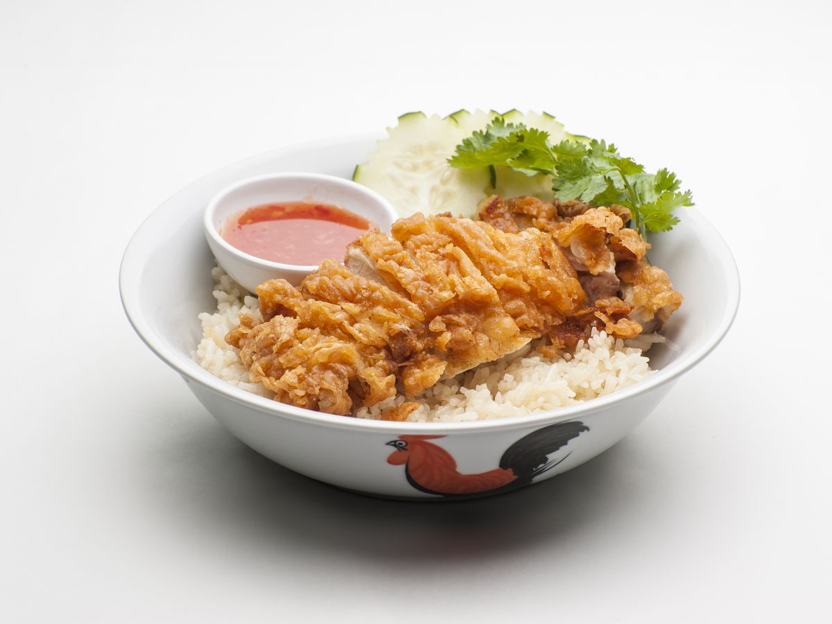 Sliced pieces of fried chicken appear over rice, next to cucumber, greens, and a side of red chili sauce