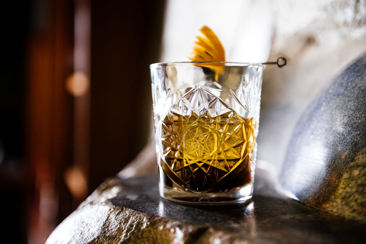 A brown cocktail in a etched glass tumbler with an orange peel garnish.