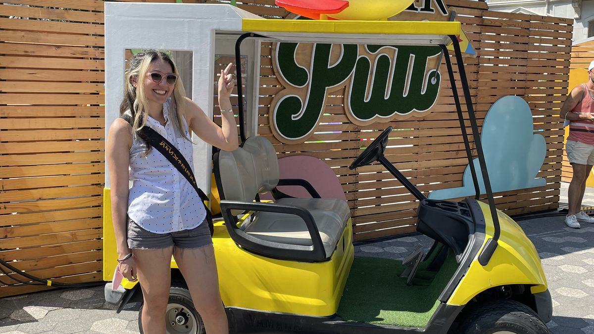 petrana stands in front of a golf cart stylized to look like the pizza planet delivery car