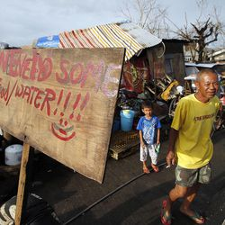 A man stands on the side of a street lined with debris in Tacloban, Friday, Nov. 22, 2013.