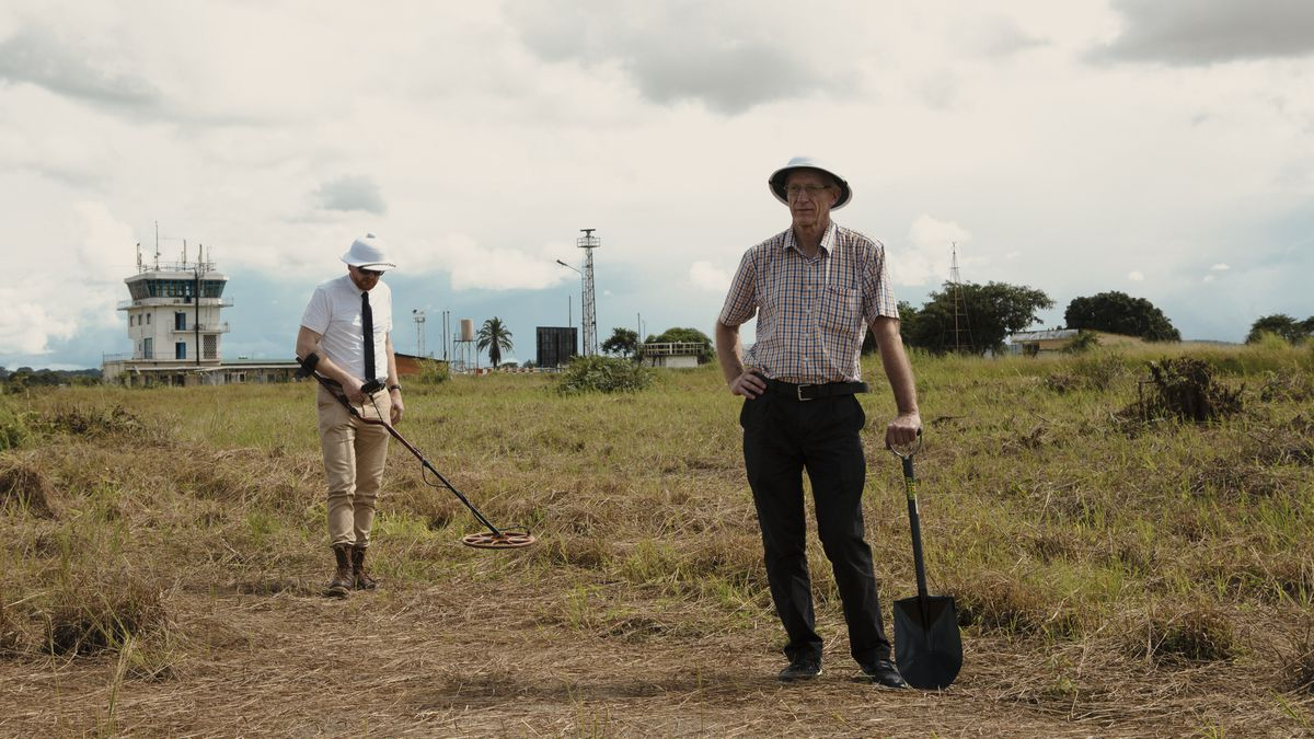 Mads Brugger and Goral Bjorkdahl run a metal detector over a field near the airport in Ndola, Zambia where the pieces of Dag Hammarskjöld's crashed airplane may be buried