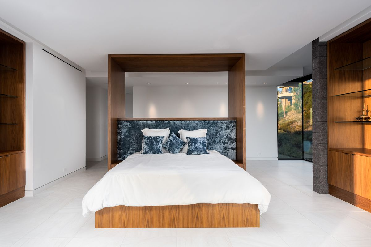 A bedroom with a wood platform bed.