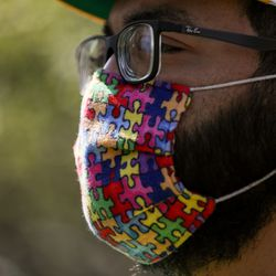 Bert Silva, whose son is on the autism spectrum, wears a mask covered in puzzle pieces, a symbol commonly associated with autism, at a rally outside the Ogden Municipal Building in Ogden on Saturday, Sept. 12, 2020. People gathered to protest and call attention to the shooting of Linden Cameron, a 13-year-old with Asperger's syndrome who was shot by police in Salt Lake City.