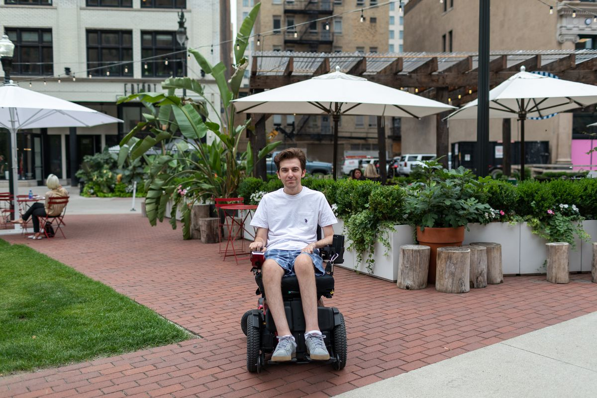 A man in an electric wheelchair faces the camera in a plaza with a brick walkway. In the background, there's planters and tables with sunbrellas.