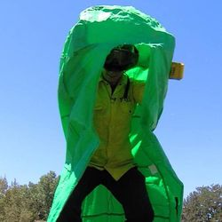 A Sandy firefighter practices getting into an emergency fire shelter Monday, July 1, 2013. Shelters are made of reflective material and can only be used once. The green shelter is used during practice.