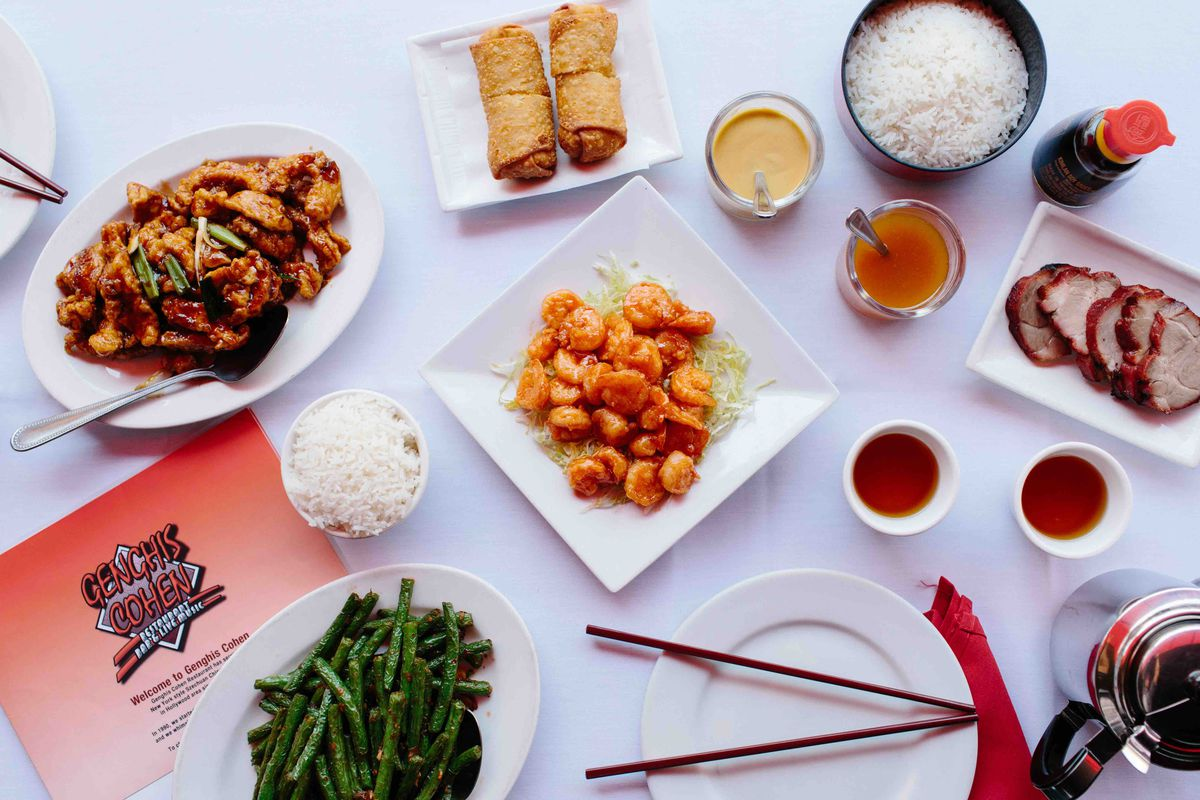 An overhead table setting with shrimp, green beans, rice, and egg rolls.