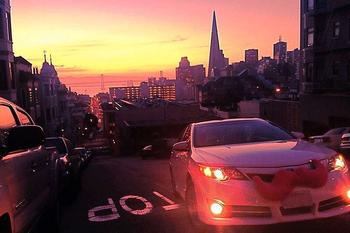 A Lyft car with pink mustache driving at sunset with the Transmamerica Pyramid in the background.