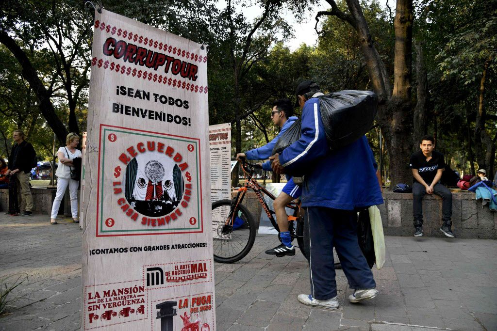 """Pedestrians walk past a banner promoting the """"Corruptour,"""" a bus that offers a sightseeing tour through different points, institutions and companies in Mexico City, related to alleged great scandals of corruption in recent Mexican history. 