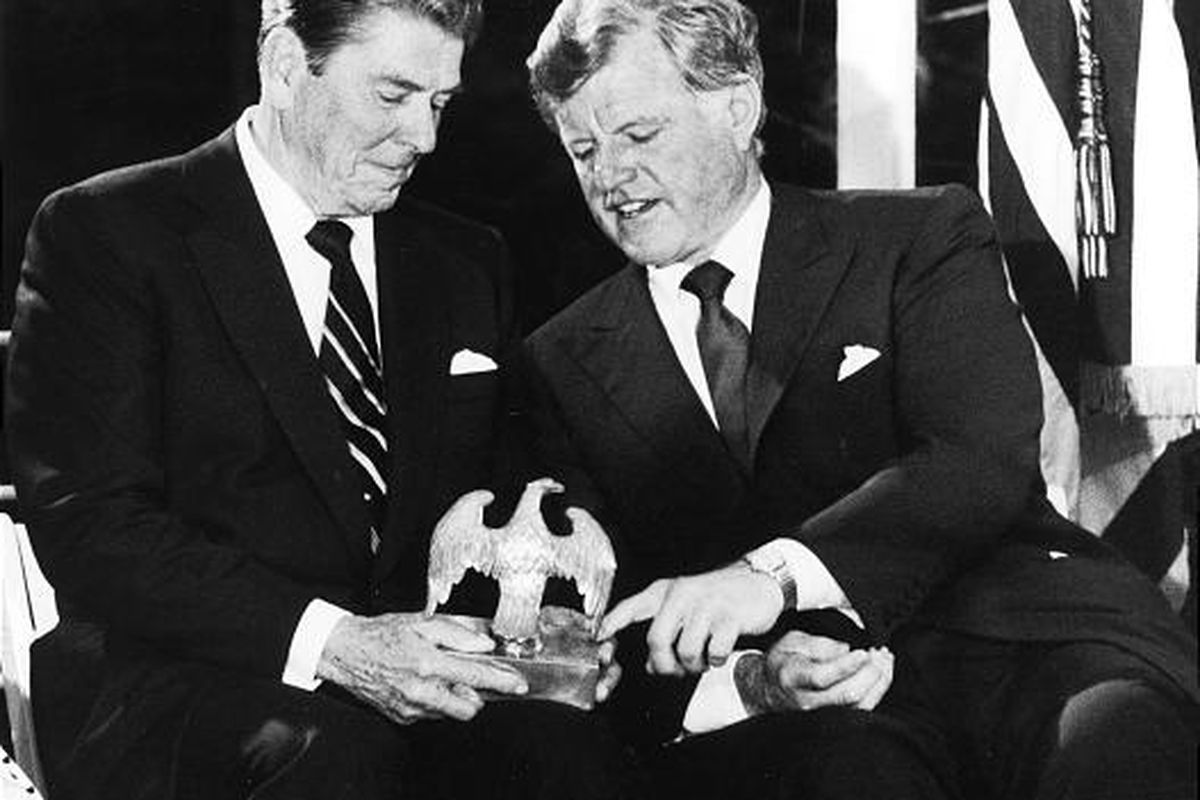 U.S. Sen. Edward Kennedy, D-Mass., talks with President Ronald Reagan, left, on June 24, 1985, as they look over an American Eagle that graced President John F. Kennedy's desk during an event for the John F. Kennedy Memorial Library at McLean, Va..