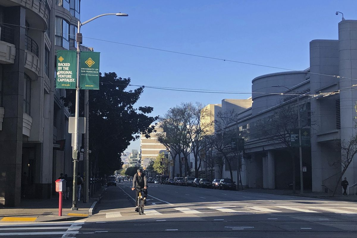 A male bike rider on a nearly empty street.