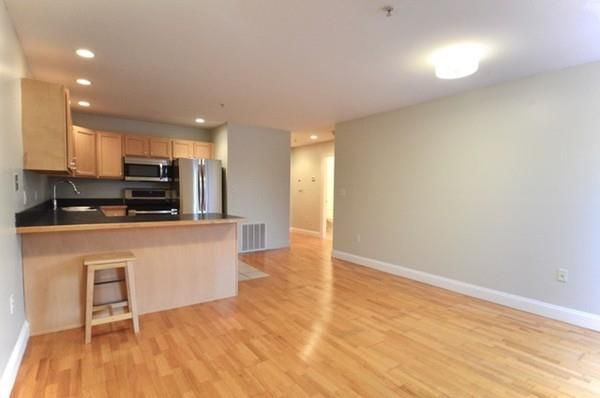 An open living room-kitchen area that's largely empty.