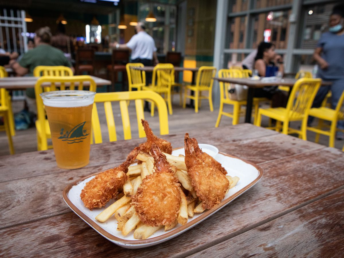 Coconut shrimp on a bed of fries on a wood table with yellow chairs in the background.