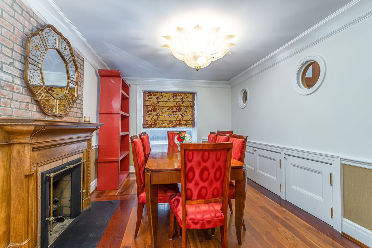 A dining area with red chairs, a wooden table, a fireplace, and light blue walls.