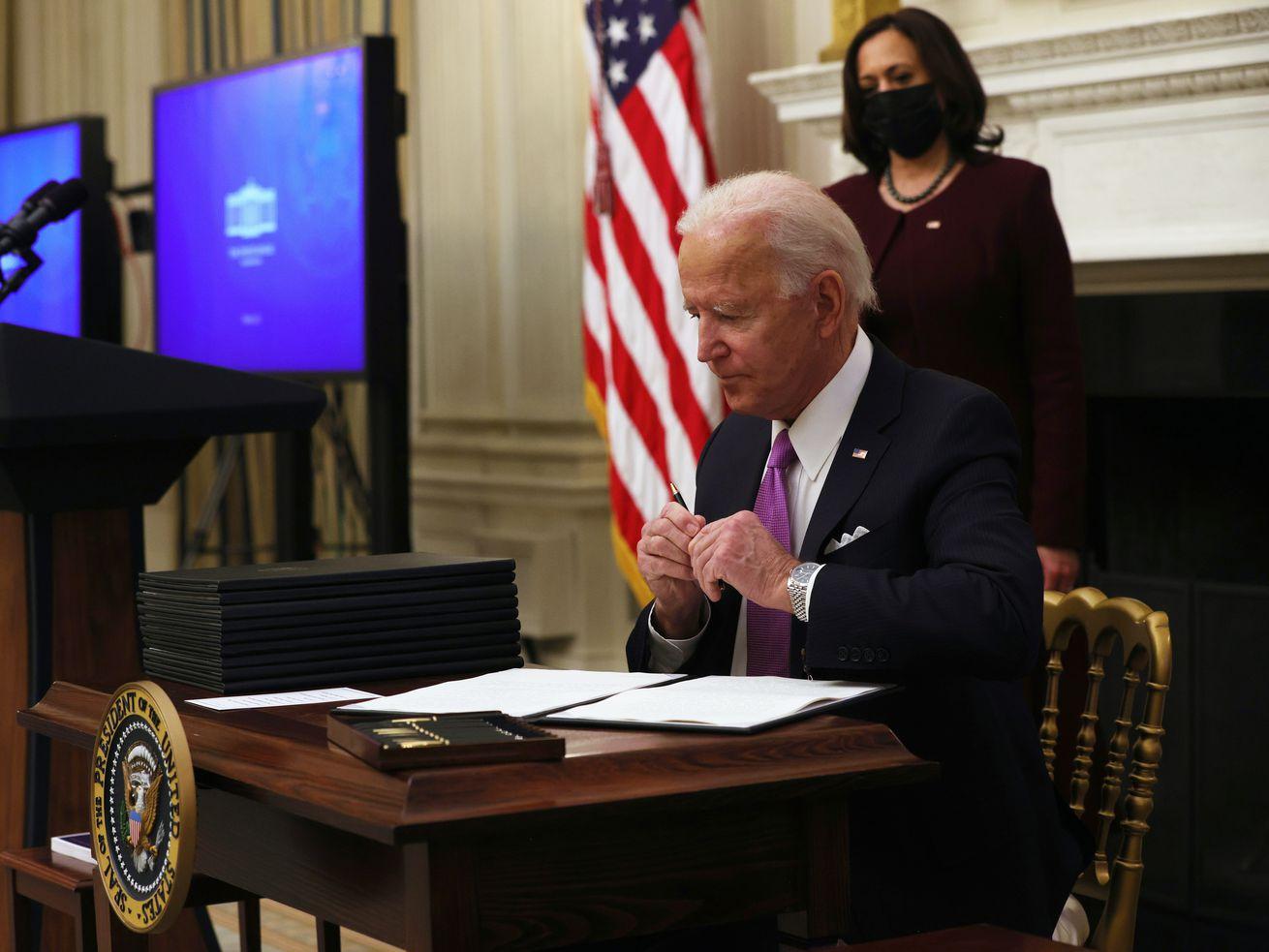 Le président Biden est assis à une table de signature de documents avec le vice-président Kamala Harris debout derrière lui à la recherche.