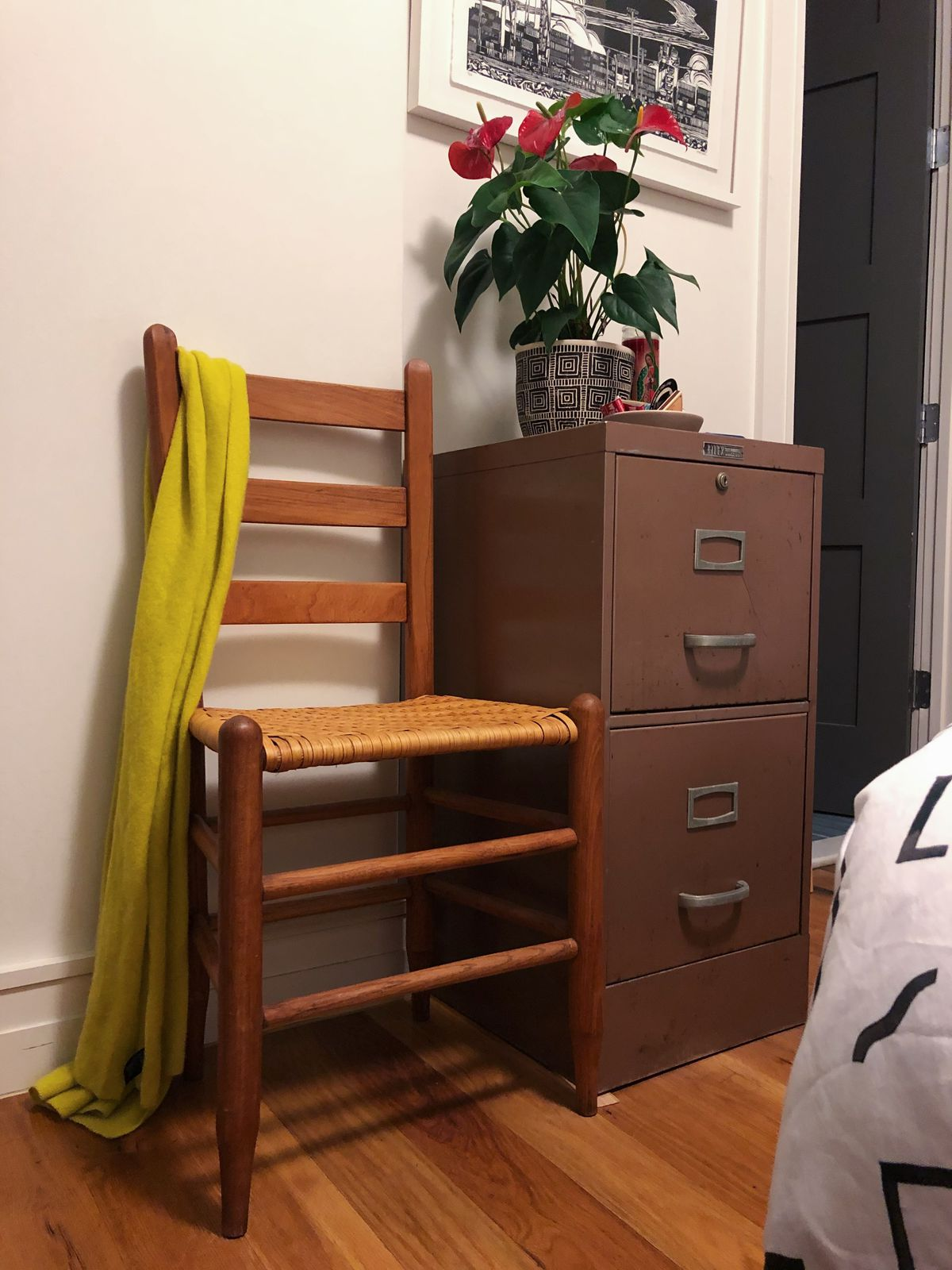 A chair with a scarf on it sits next to filing cabinet.