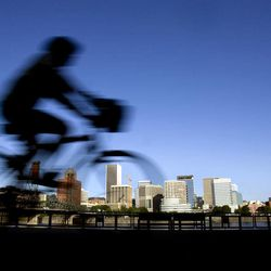 FILE-  In this July 10, 2008 file photo, a bicyclist is a blur traveling along the east bank of the Willamette River as the downtown skyline is bathed in early morning sunlight in Portland, Ore. Researchers at Portland State University found that the Portland atmosphere and culture is a magnet for the young and college educated, even though a disproportionate share of them are working in part-time jobs or positions that don't require a college degree.