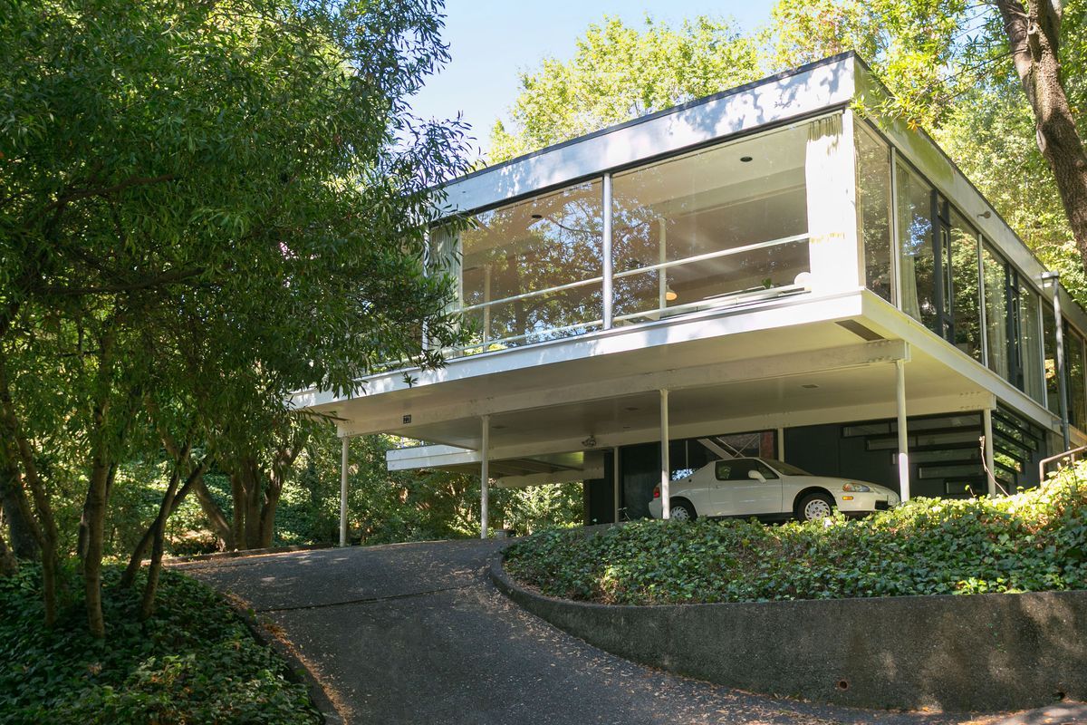 A sleek glass-walled pavilion on stilts cantilevers over sloping site.