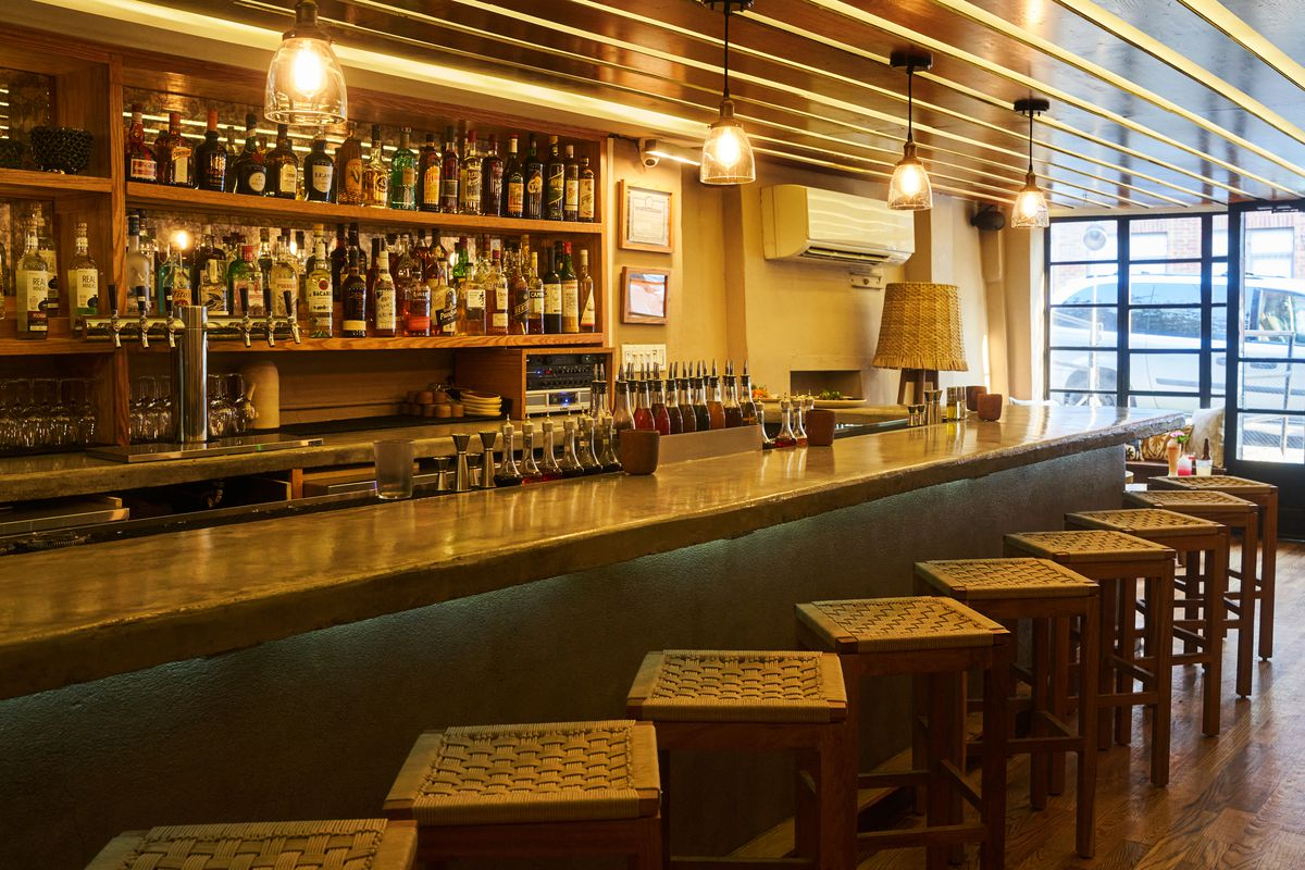 Wooden stools are pulled up to a lengthy bar, which is stocked with tequilas, mezcals, and liquors