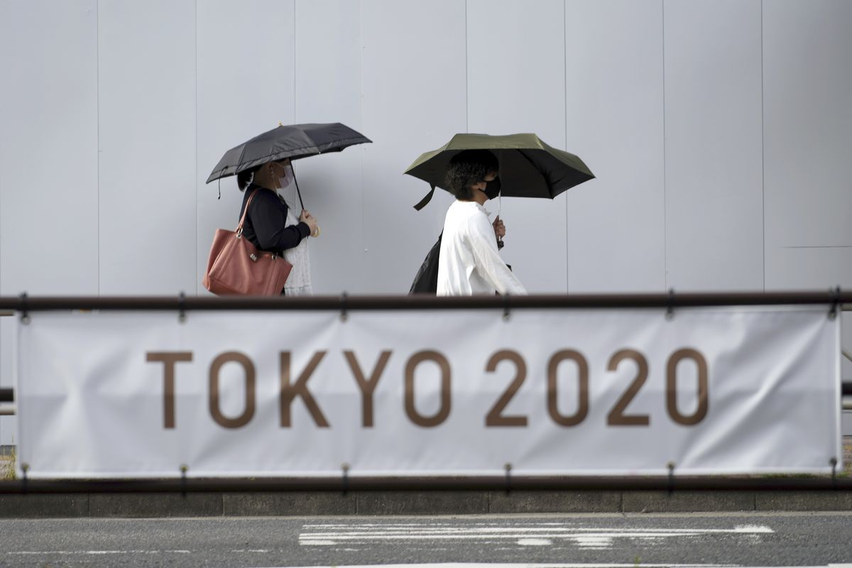 People wearing masks to help protect against the spread of the coronavirus walk near a banner promoting the Tokyo Olympics.