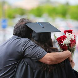 A Salt Lake Community College graduate gets a hug at the school's commencement ceremony at the Maverik Center in West Valley City on Friday, May 6, 2016.