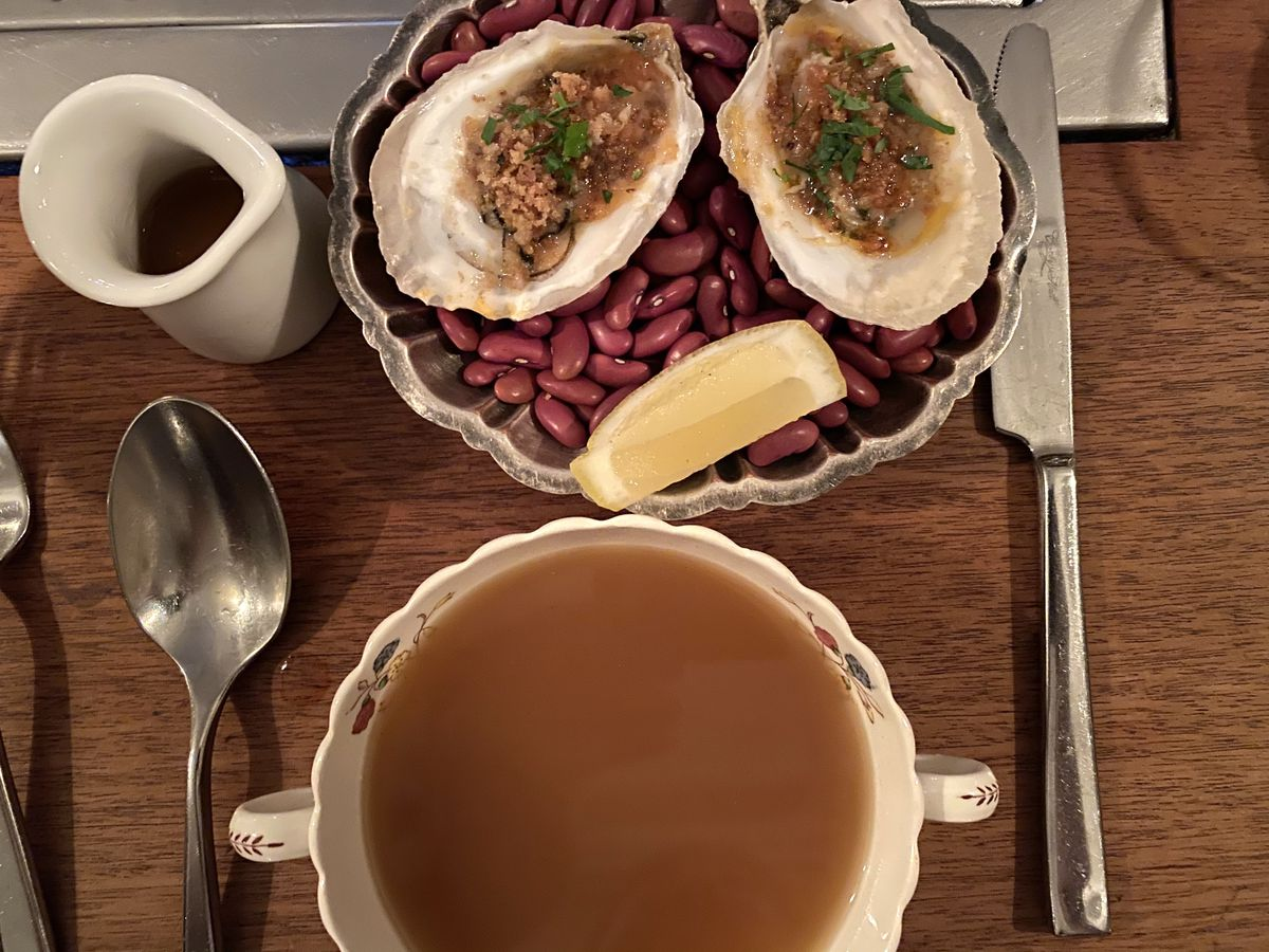 Two broiled oysters with breadcrumbs sit on a bed of dried beans at Anton's in the West Village; a cup of chicken broth lies below