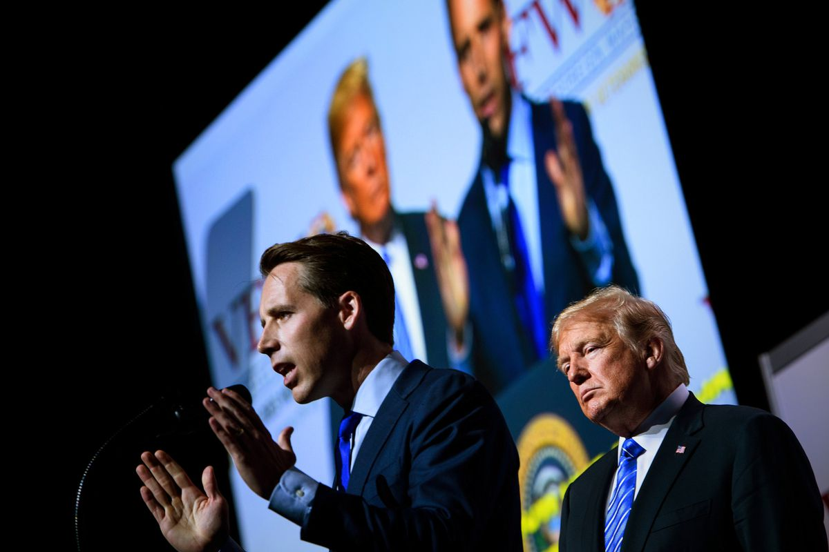 Josh Hawley speaking at a podium with President Donald Trump standing behind him. A giant video screen in the background shows the two men from another angle.
