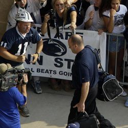 Penn State NCAA college football coach Bill O'Brien carries his bags as he leads his team into Beaver Stadium for their season opener against Ohio in State College, Pa., Saturday, Sept. 1, 2012.
