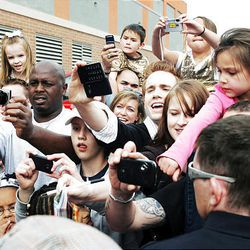 """Fans reach to get photos of Miley Cyrus, who made an appearance Friday for a premiere of her movie, """"Hannah Montana,"""" at the Megaplex 20 in South Jordan."""