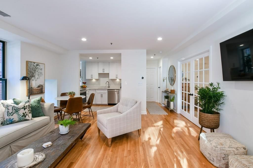 A long, open living room-dining room area leading to a kitchen, and there's furniture throughout.