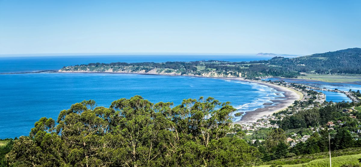 An aerial shot of Bolinas which is in front of the blue Pacific Ocean.
