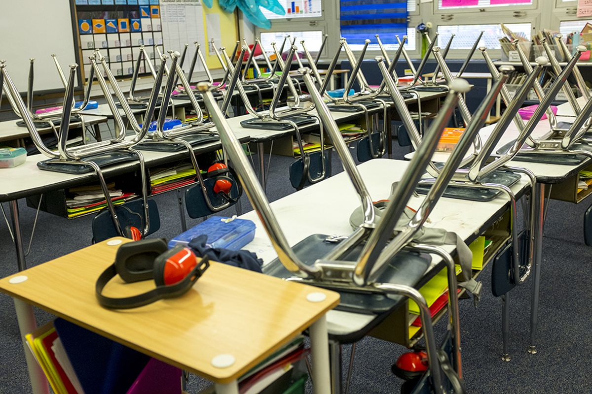 An empty classroom with chairs upside down on desks.