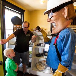 In this June 28, 2013 photo, owner Craig Christiansen, center, and Rocky Mountain Power's mascot Slim the Lineman welcome Seth Robinson, 5, of Spanish Fork, to The Chocolate in Orem, Utah. Christiansen received a message that power was going to be shut off at his business if he did not respond immediately with a payment. Christiansen called Rocky Mountain Power before returning the message. He found out the person who called was a scammer. On Friday, representatives from Rocky Mountain Power decided to purchase 120 snickerdoodles from Christiansen to thank him for helping to spread the word of how to avoid scammers. (AP Photo/Daily Herald, Spenser Heaps)