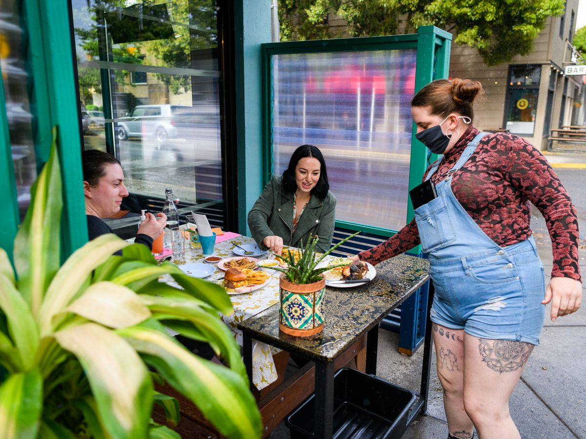 A person in overalls drops off a plate of food at a table outside Oma's Hideaway