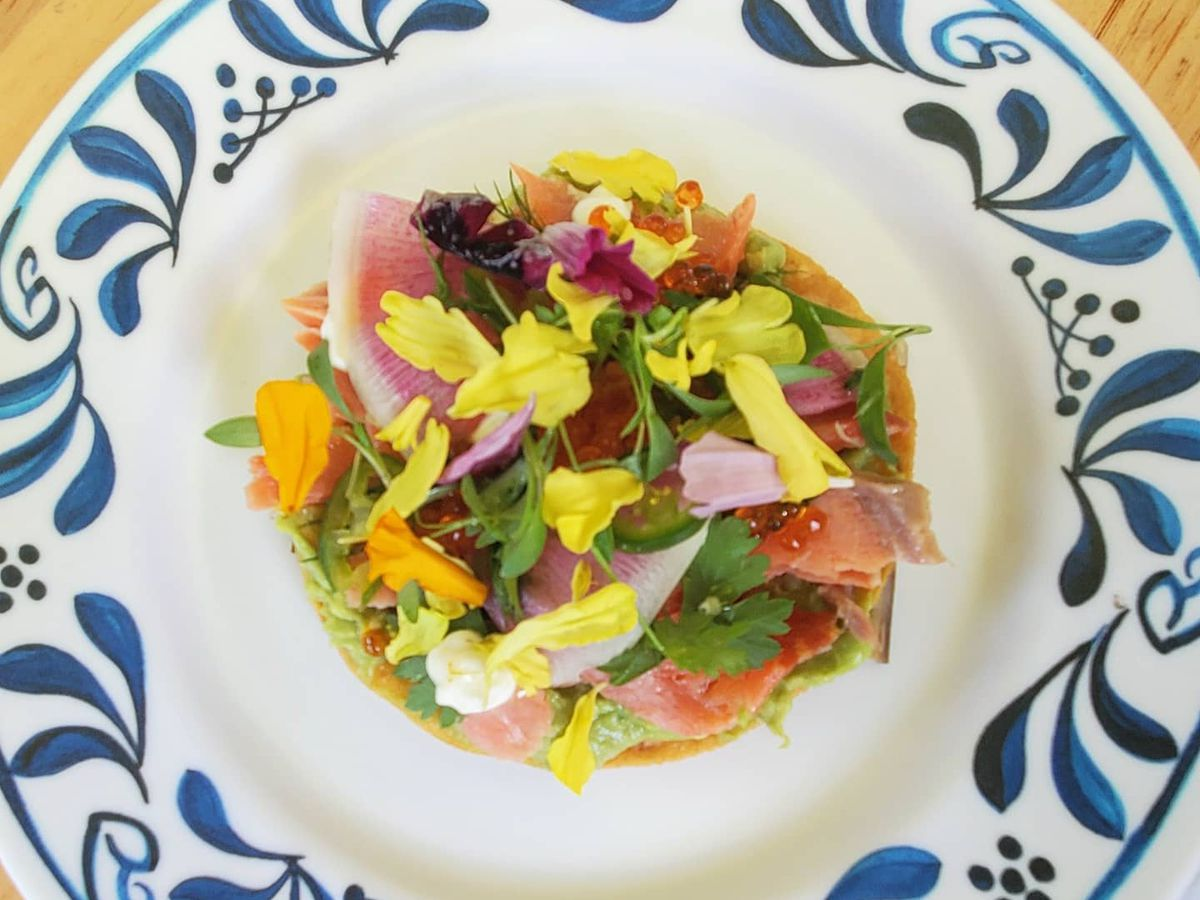 A smoked trout tostada full of flowers and radishes from Muchas Gracias