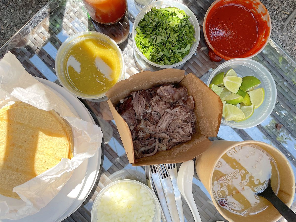 Takeout barbacoa accompanied by consommé, tortillas, onions, cilantro, and green and red salsa