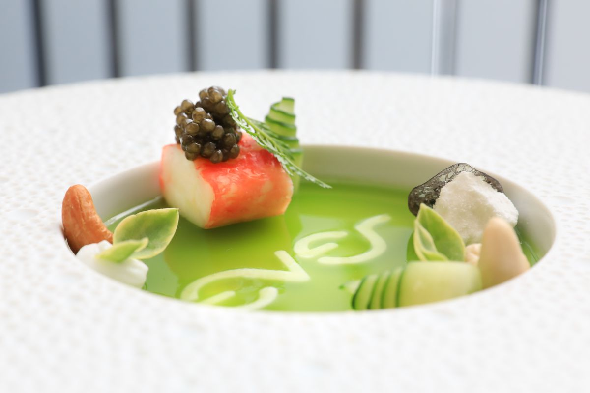A white bowl holds a dish of Osetra caviar, crab, cucumber, and citrus lace