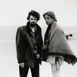 """In this March 1976 publicity photo released by Lucasfilm Ltd. & TM, director, George Lucas, and actor, Mark Hamill, who portrays young Luke Skywalker, are shown on the salt flats of Tunisia during principal photography of the original """"Star Wars."""""""