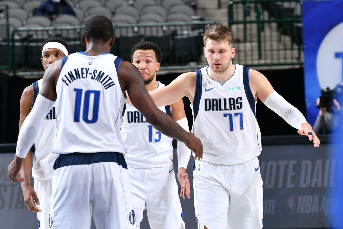 Dorian Finney-Smith and Luka Doncic of the Dallas Mavericks high five during the game against the Portland Trail Blazers on February 14, 2021 at the American Airlines Center in Dallas, Texas.