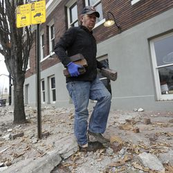 Fred Moesinger, owner of BTG Wine Bar and Caffe Molise in Salt Lake City, picks up bricks among debris that fell from his building after a 5.7 magnitude earthquake centered in Magna hit early on Wednesday, March 18, 2020.