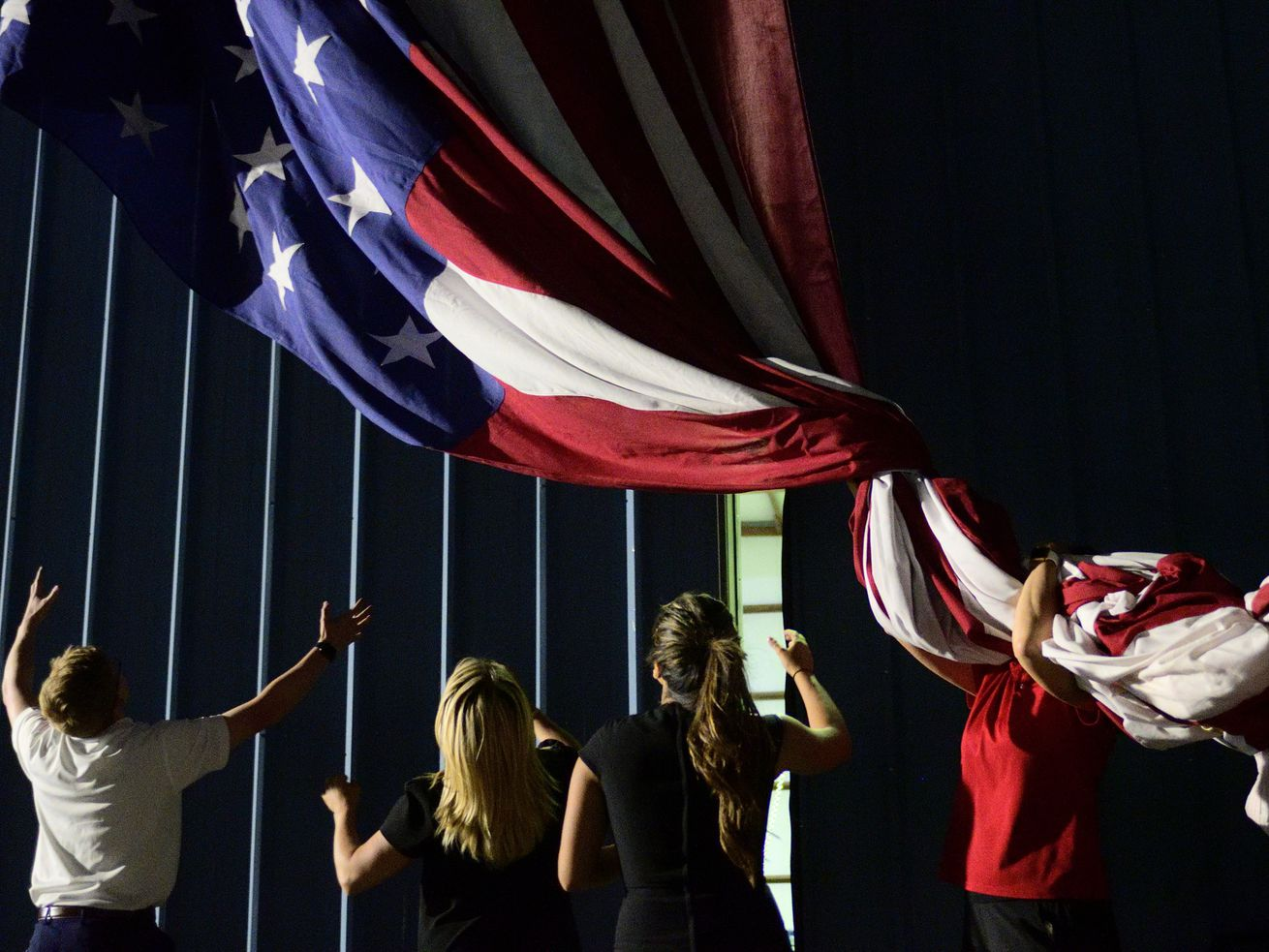 A large American flag, part of the decoration, is lowered by campaign aids after a MAGA rally with US President Donald J. Trump at the Williamsport Regional Airport, in Montoursville, PA, on May 20, 2019.